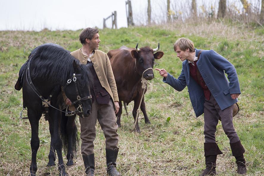 Pferd gegen Kuh: Hans (Anton Spieker, r.) tauscht unvorteilhaft mit dem Bauern (Max Hopp) / © NDR/Georges Pauly