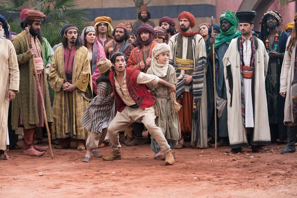 Good Boy: Aladdin (Mena Massoud) stellt sich schützend vor zwei Kinder – und rettet ihnen so das Leben / © Disney
