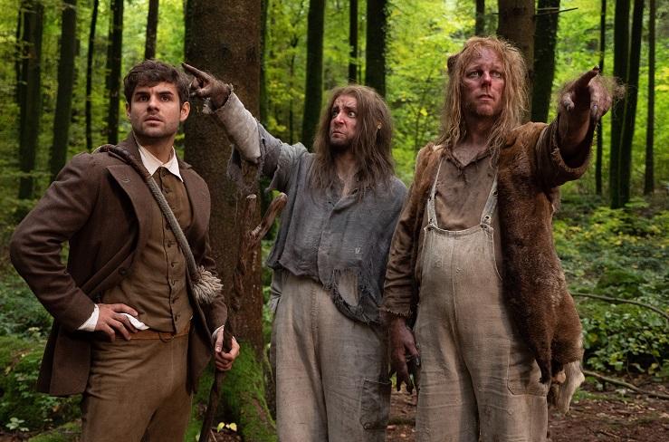 Vorbilder: Hans (Lucas Reiber) trifft zwei Waldschrate (Jonas Minthe, Stephan Tölle). Sie erinnern in Maske und Kostüm an typische Nebenfiguren des osteuropäischen Märchenfilms / © BR/Michael Boxrucker